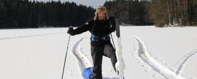MIkko PEltola näyttää suksenpohjaa, johon on paakkuuntunut paljon lunta.
