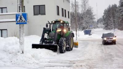 En traktor röjer bort snö på en trattoar i Svartå.