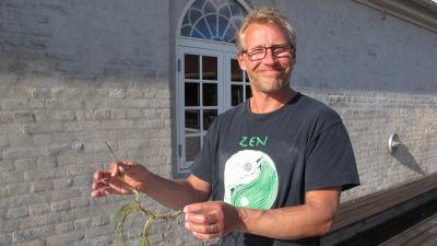 Christoffer står vid en stor balja och håller i någon form av sjögräs.
