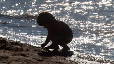 Ett barn leker vid vattnet på Sandudds badstrand i Helsingfors