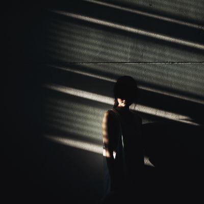Ung kvinna lutar mot en vägg i mörker