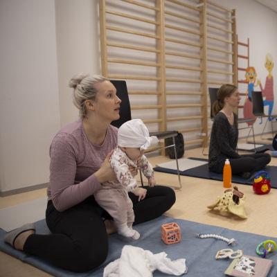Äitejä vauvojen kanssa pienessä voimistelusalissa.