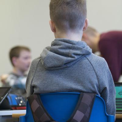 Pojke sitter i klassrum