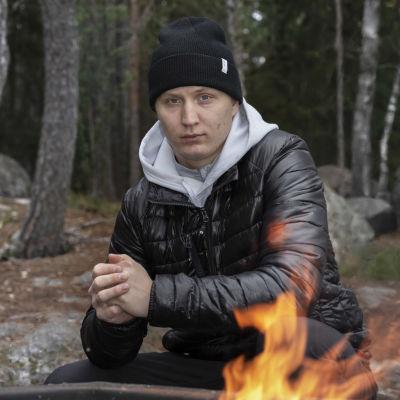 Joel Kiviranta istuu nuotion ääressä metsässä.
