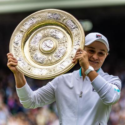 Ashleigh Barty poseerasi Wimbledonin tennisturnauksen voittolautasen kanssa.