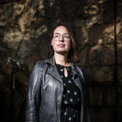 Kvinna står och tittar åt sidan, mot en mörk bakgrund.