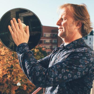 DJ Bunuel håller upp en vinylskiva.