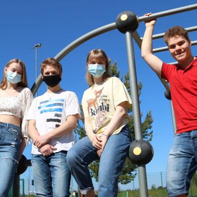 Neljä nuorta poseeraa kiipeilytelineen juurella.