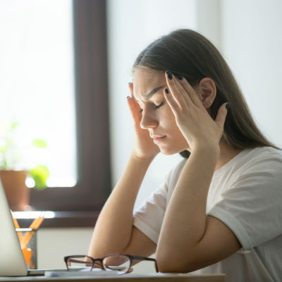 En flicka sitter vid en dator och ser förtvivlad ut.