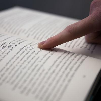 avoinainen kirjan aukeama tummalla taustalla, lukija seuraa tekstin rivejä sormellaan