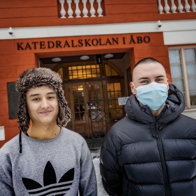 Till vänster en ung man med grå collegetröja och pälsmössa och till höger en ung man med mörkblå vinterrock och munskydd.