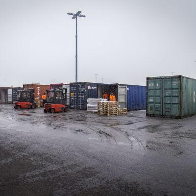Containrar uppradade på en regnblöt kaj i Nordsjö hamn.