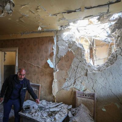 Kaksi miestä tutkii tuhoja huoneessa, jonka seinässä on valtava pommin tekemä aukko.