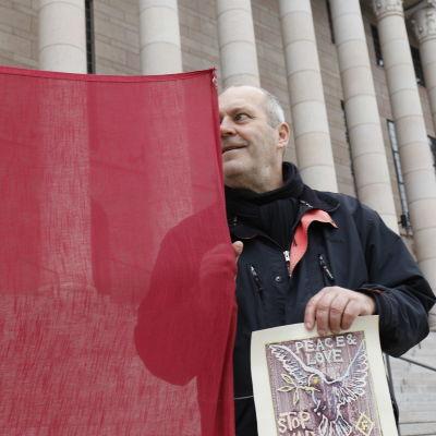Kuvataiteilija Olavi Fellman seisoo Eduskuntatalon portailla ja pitää kiinni punaisesta banderolista.