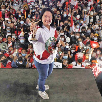 Keiko Fujimori seisoo hymyillen puhujanlavalla esitellen pientä patsasta, joka esittää Jeeusta ristillä. Toisessa kädessään hänellä on mikrofoni. Hänellä on yllään valkoinen pusakka ja siniset farkut. Taustalla näkyy yleisömerta.