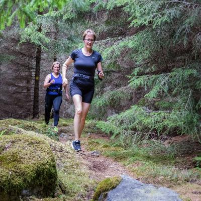 Kaksi naista juoksee metsäpolulla