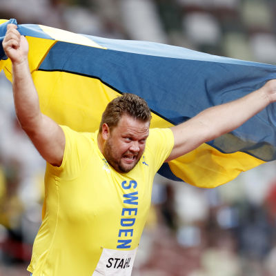 Daniel Ståhl rusar i väg med Sveriges flaggar unt axlarna.