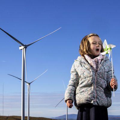 Kolme suurta tuulimyllyä seisoo maisemassa sinistä taivasta vasten. Etualalla pikkutyttö puhaltaa kädessään olevaan tuulihyrrään.