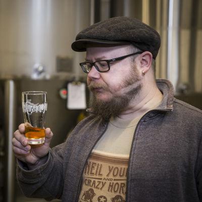 Grundaren av Fiskars bryggeri, Jari Leinonen, står med ett ölglas i handen.