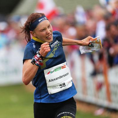 Orienteraren Tove Alexandersson löper i mål i en mörkblå dräkt och kartan i vänsterhand.
