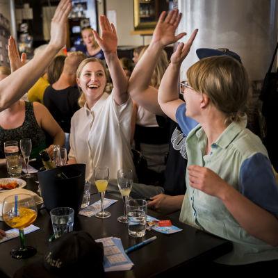 Joukko nuoria antaa toisillee yläfemmoja bingoiilllassa Ravintola Oivassa.