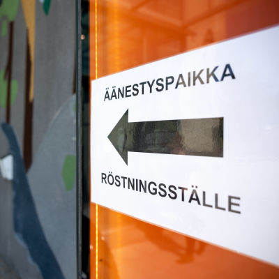 """Kyltti ulkoseinässä, jossa lukee """"äänestyspaikka"""". Kyltin keskellä on iso nuoli kuvan oikealta vasemmalle."""