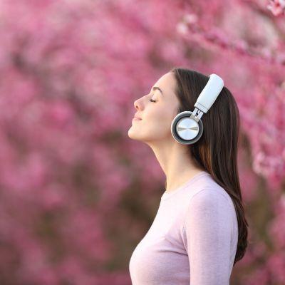 En kvinna med hörlurar på sig fotograferad från sidan. Hon står utomhus i ett fält av rosa blommor och träd.