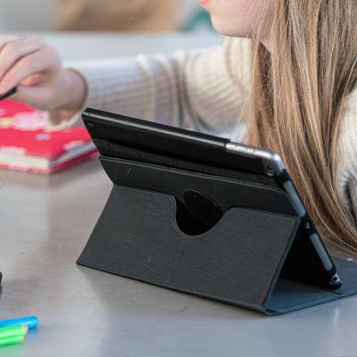 En ung flicka sitter vid ett bord och studerar. Framför sig har hon en surfplatta, böcker och pennor.