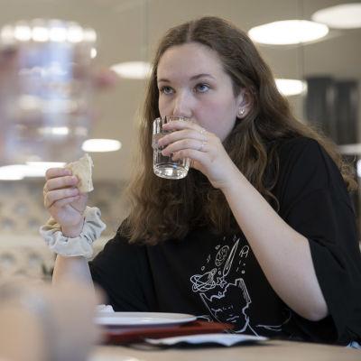 Kvinnlig skolelev äter skollunch och dricker ur ett vattenglas