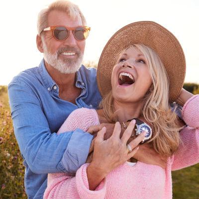 Äldre man i solglasögon omfamnar leende yngre kvinna i solhatt