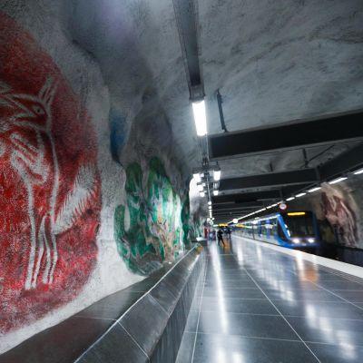 Näkymä Tenstan metroaseman laiturilta. Kuvassa iso seinämaalaus ja asemalla seisova metrojuna.