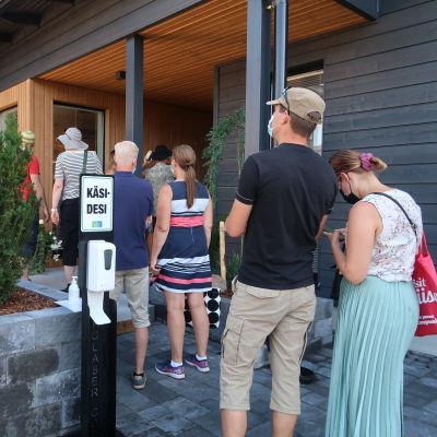 Bild av kö till ett av husen på bostadsmässan i Lojo. Bredvid kön finns en station för att desinfiera händerna.