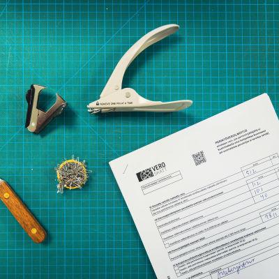 Kansallisarkiston työkaluja joita käytetään niittien poistoon asiakirjoista.