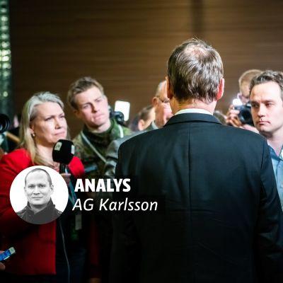 Juha Sipilä står med ryggen mot kameran, omringad av journalister.