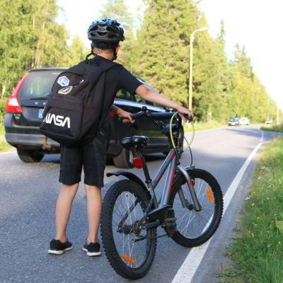 Auto ohittaa pyörää taluttavan lapsen
