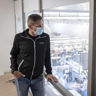 Pekka Karhu katselee lihanleikkaajia lasin takaa.