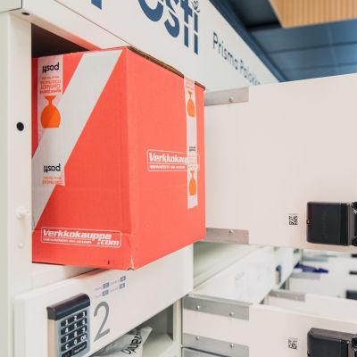 Verkkokauppa.comin paketti odottaa pakettiautomaatin luukun sulkemista.