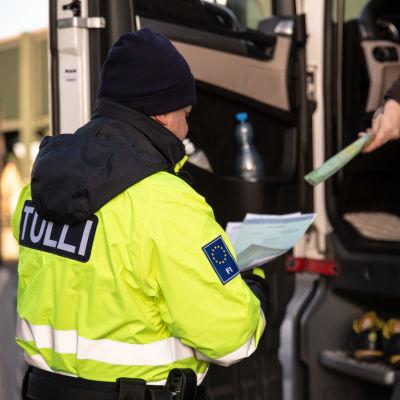 En lastbilschaufför räcker dokument till tullens tjänsteman i overall.