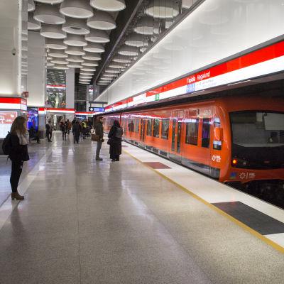 Ihmisiä ja metrojuna Tapiolan metroasemalla.