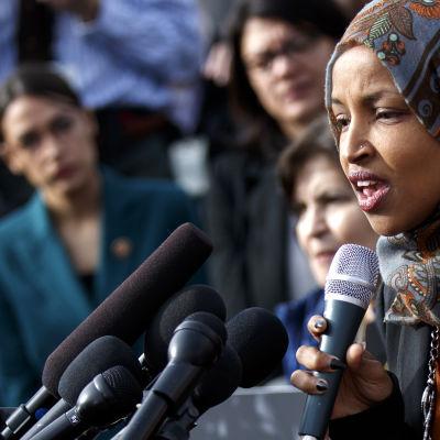 Kongressledamoten Ilhan Omar med huvudduk framför mikrofonen. I bakgrunden suddigt Alexandria Ocasio-Cortez