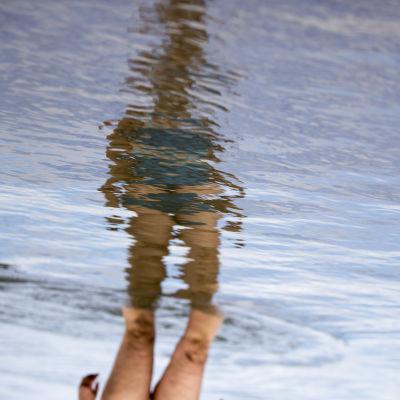 uimari kävelee vedessä, saa kääntää oikeinpäin