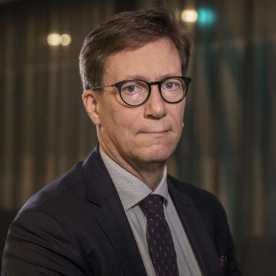 Mikko Pietilä, en man med glasögon, blå kavaj och slips, tittar in i kameran.