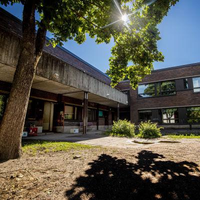 Brungrå betongbyggnad i solsken.