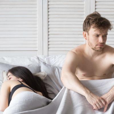 Kvinna sover i en säng, en man sitter vaken och ser besviken ut