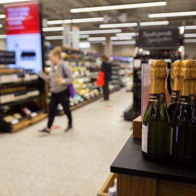 Alkon myymälän sisällä etualalla pieniä kuohoviinipulloja rivissä, taustalla epäterävänä näkyy asiakkaita, nainen on pullo kädessä kävelemässä kohti kassaa, mies punaisen kanssa tutkii pulloa hyllyn edessä.
