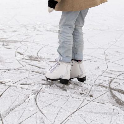 Ett barn med ljusa jeans står på isen i ett par vita skridskor.