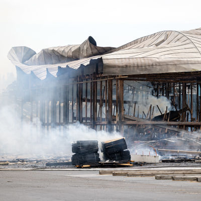 Mustola Timber -sahan varastorakennus tuhoutunut täysin tulipalossa, savua nousee raunioista.