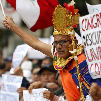 Man iklädd orange t-skjorta och en del guldrekvisita flaggar med Perus flagga.