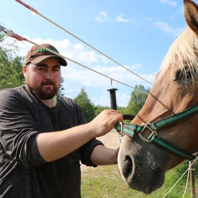 Lippalakkipäinen Santeri Oikarainen pitelee kiinni hevosen riimuista.