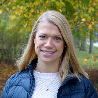 Doktorand Malin Göransson utomhus i park med höstgula träd och buskar